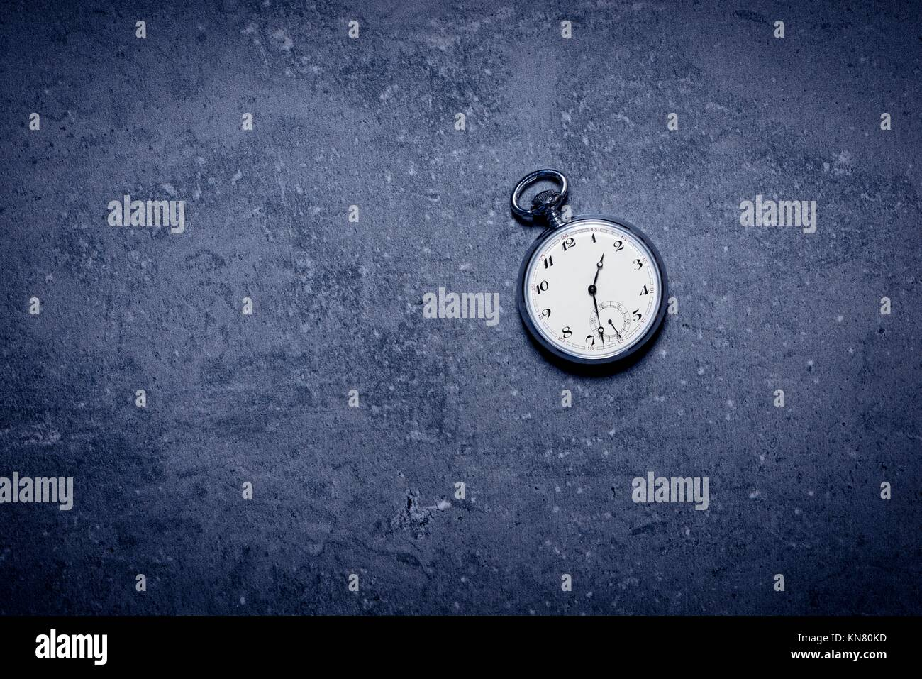 Alte Taschenuhr auf steinernen Tisch in der Dunkelheit. Symbol der Zeit-, Termin- und Nostalgie. Stockbild