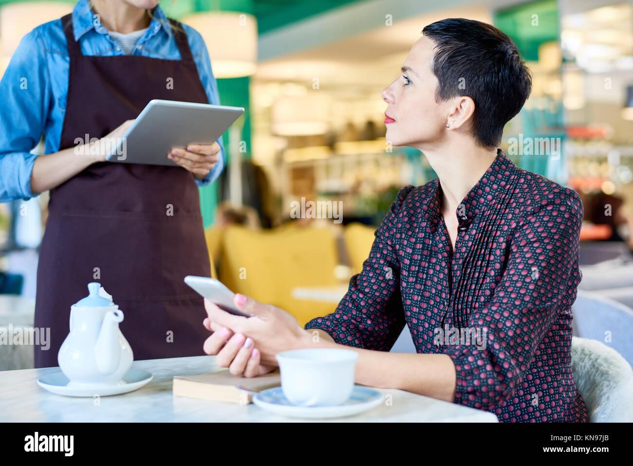 Elegante Frau Essen bestellen im Cafe Stockbild
