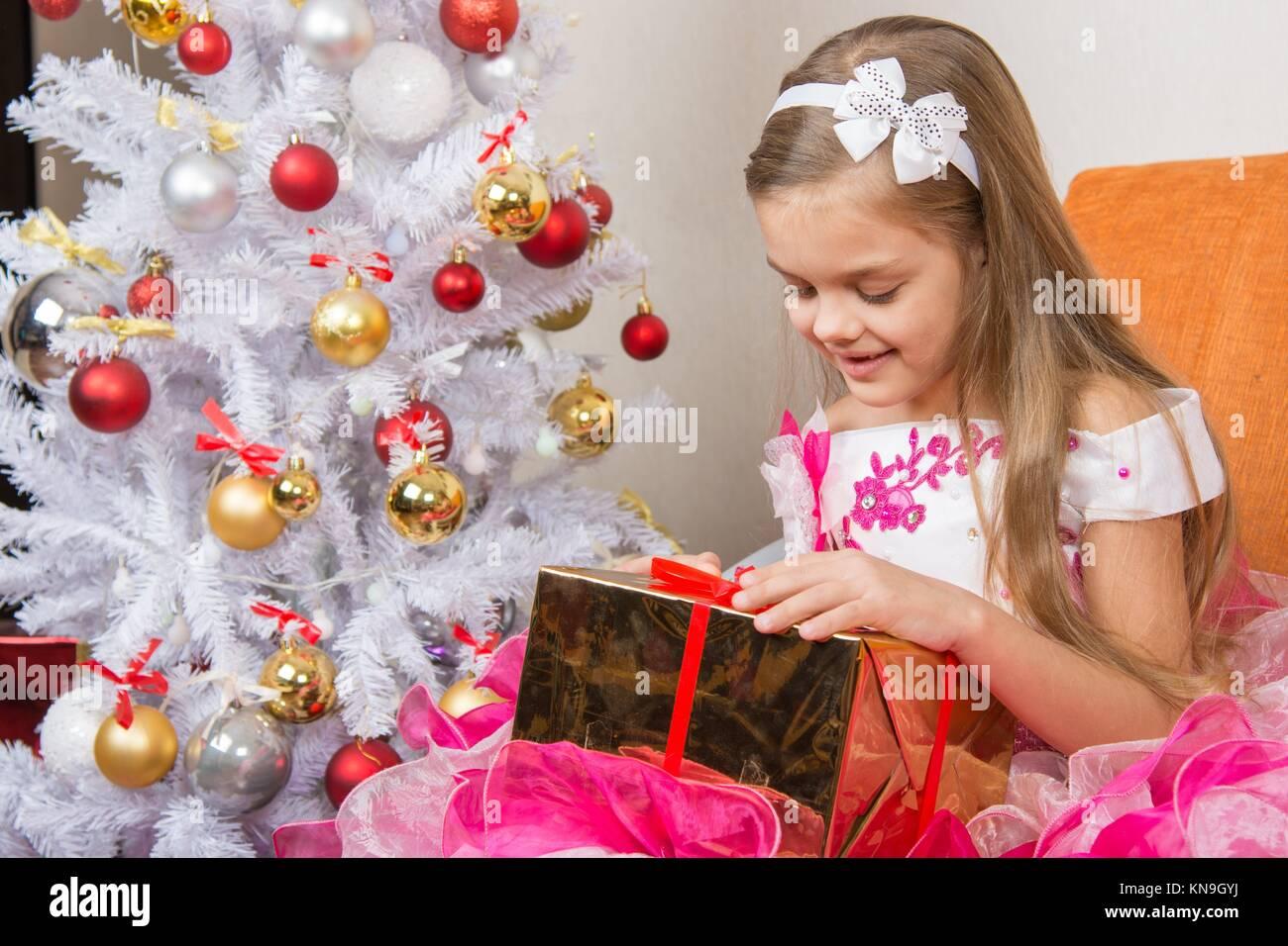7-jährige Mädchen in einem schönen Kleid erwägt, ein Geschenk von ...