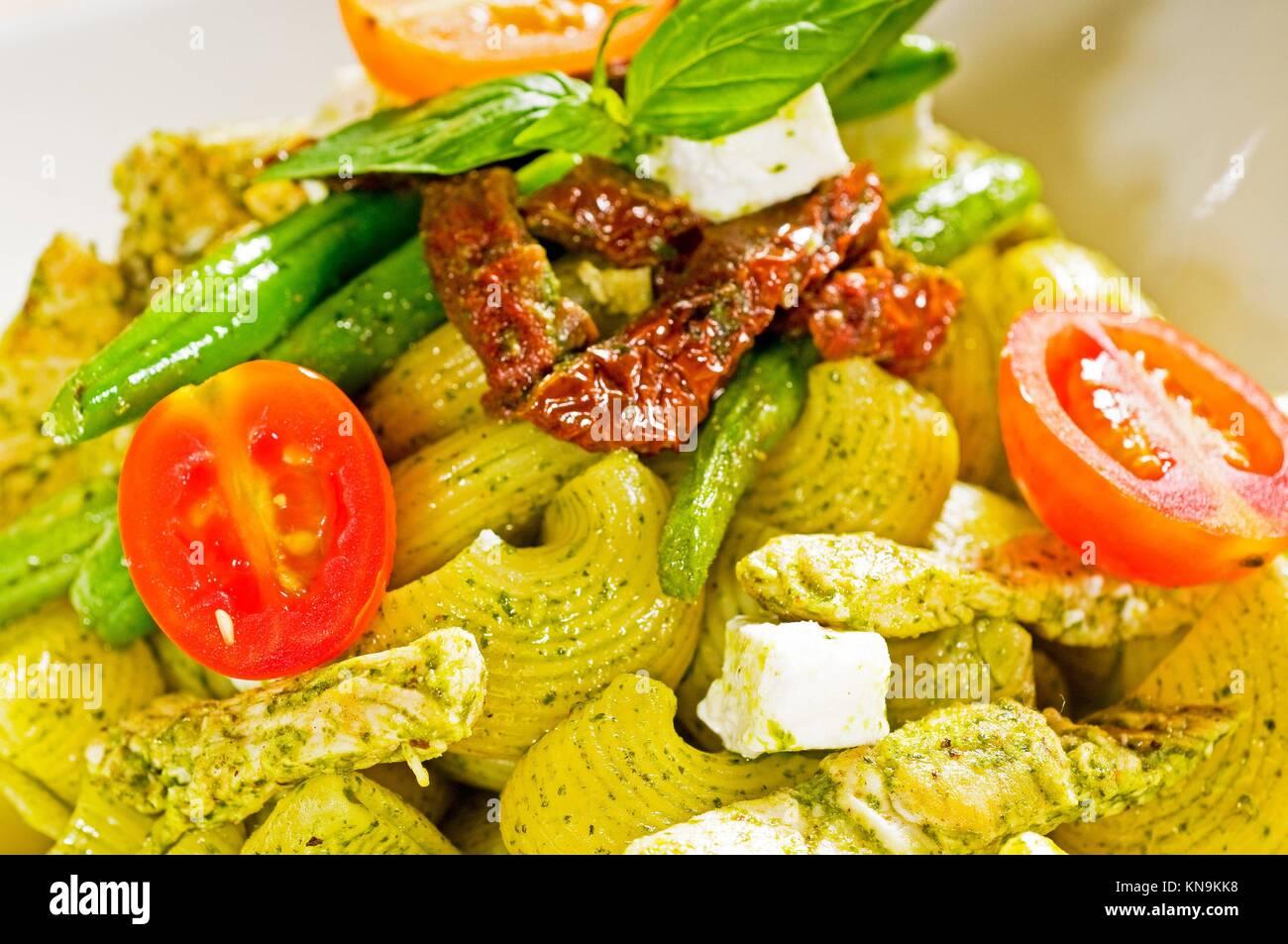 Frische lumaconi Nudeln und Pesto Sauce mit Gemüse und getrockneten Tomaten, typisches italienisches Essen. Stockbild
