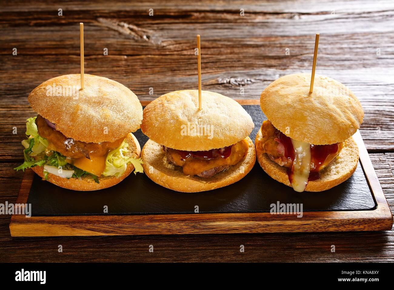 Burger In Einer Reihe Auf Einem Schiefer Und Holz Tisch Stockfoto