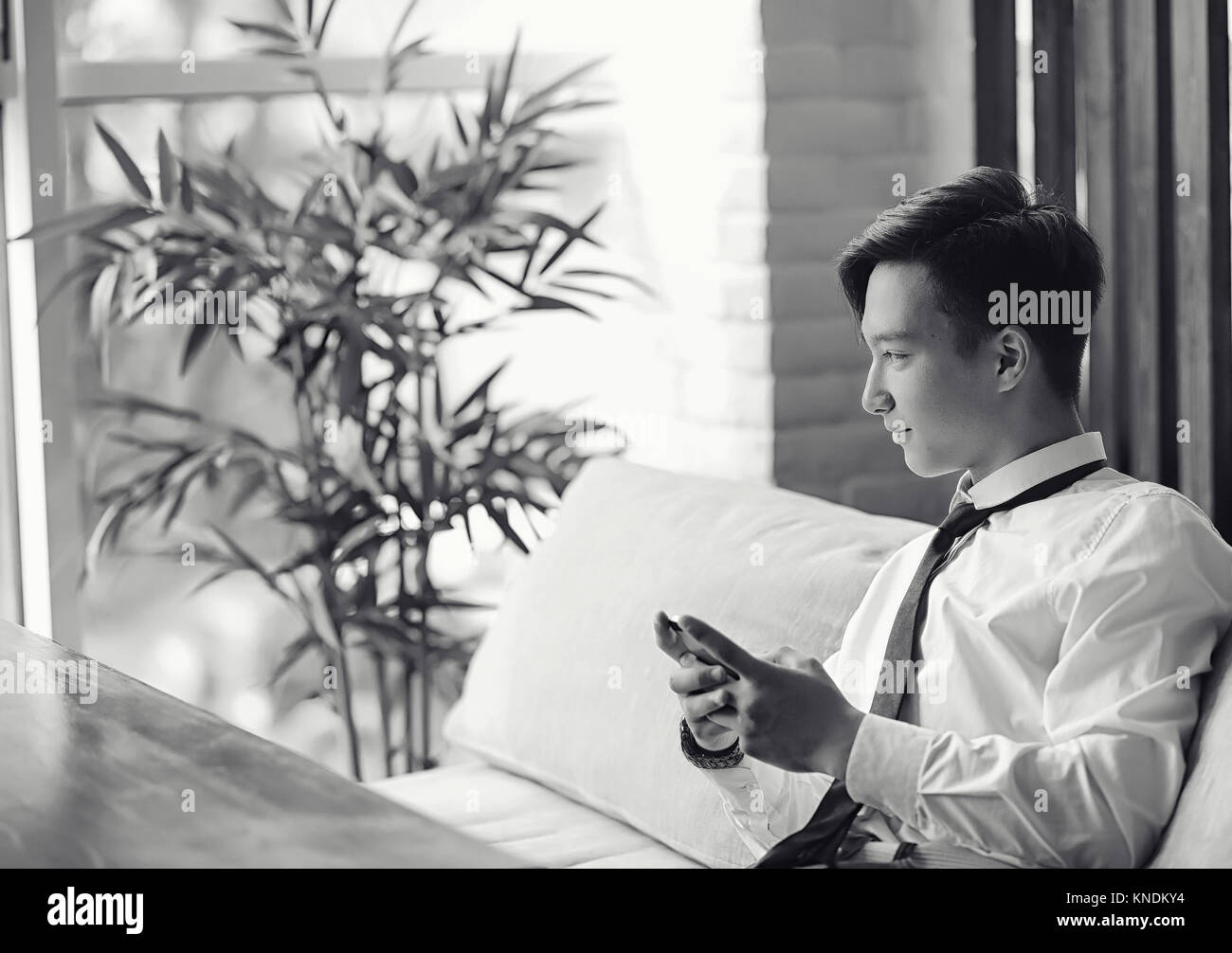 Ein junger asiatischer Geschäftsmann wartet auf einen Partner in einem Café. Bu Stockbild