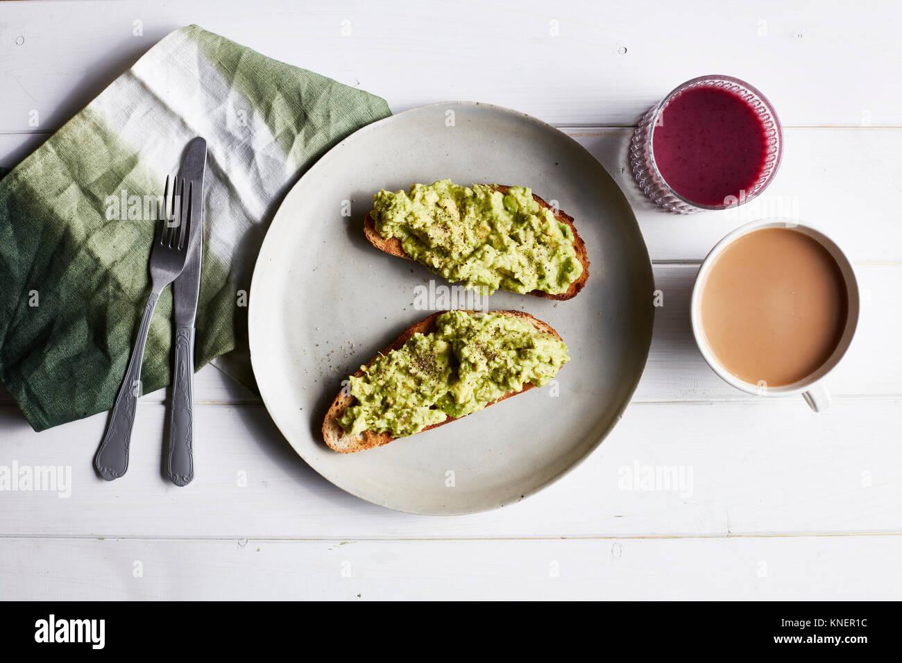 Avocado auf Toast auf weiße Platte, Ansicht von oben Stockbild
