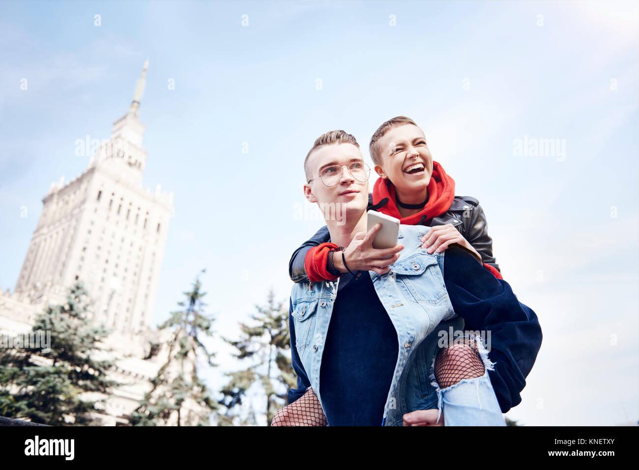 Junger Mann, der lacht Freundin eine piggy zurück in der Stadt Stockbild