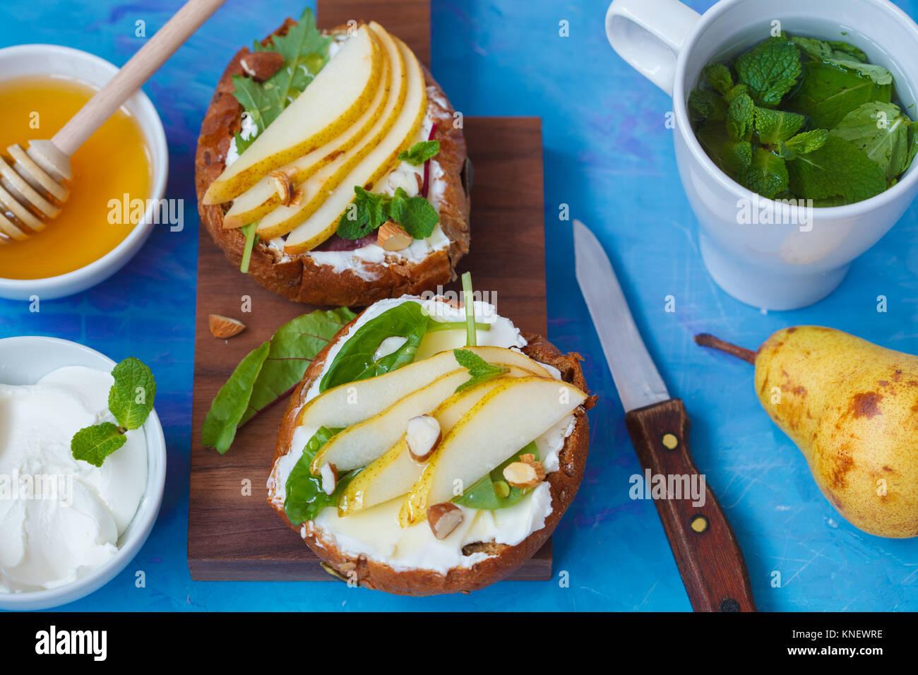 Sandwiches mit Hüttenkäse, Honig, Birne und Walnüsse mit einem Pfefferminztee. Europäische gesunde festlichen Frühstück Stockfoto