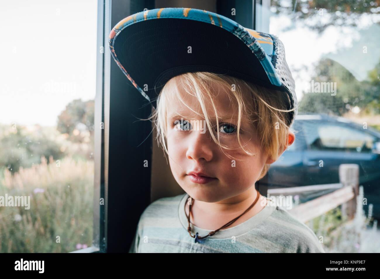 Portrait von blonder junger Mann, Baseball Cap von Fenster Stockfoto