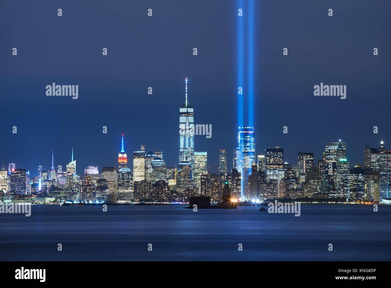 Die beiden Balken des Tribute in Light mit Wolkenkratzern von Lower Manhattan bei Nacht von New York Harbor. Financial Stockfoto