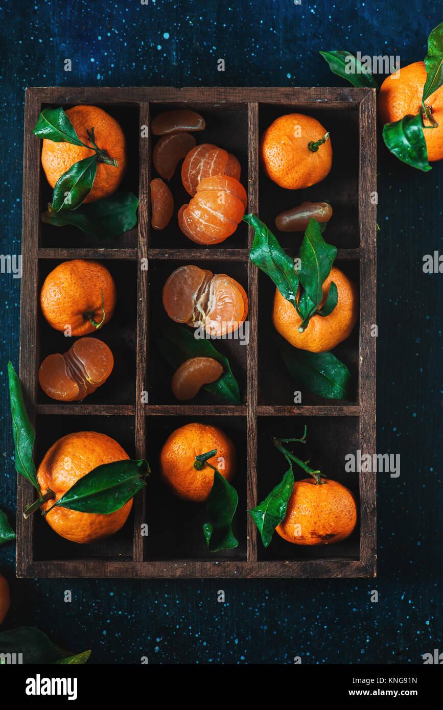 Mandarinen in einer Holzkiste auf einem dunklen Hintergrund. Ein Sortiment von Clementinen mit grünen Blättern. Stockbild