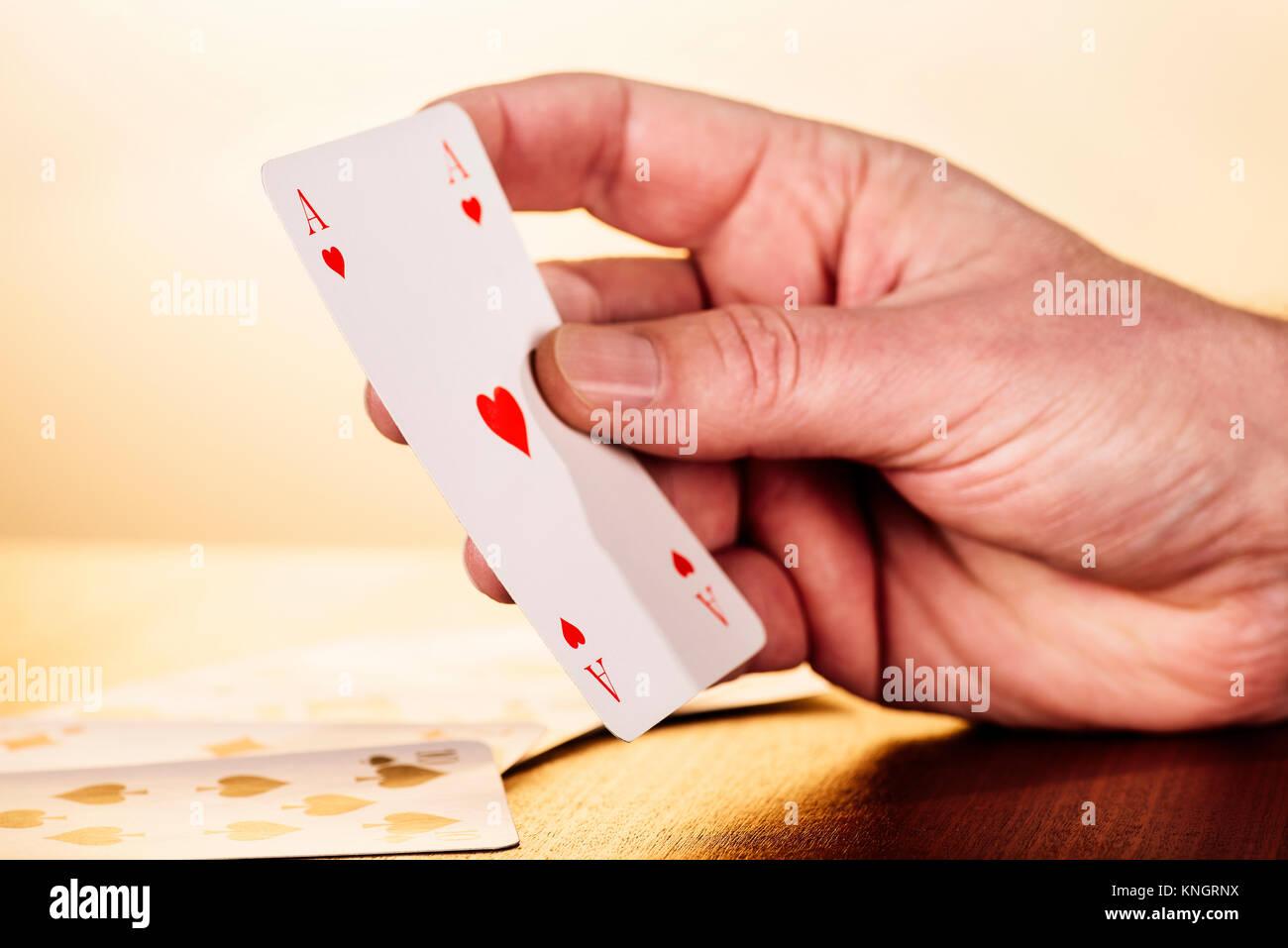 Nahaufnahme einer Hand, die ein Herz Ass Spielkarten. Stockbild