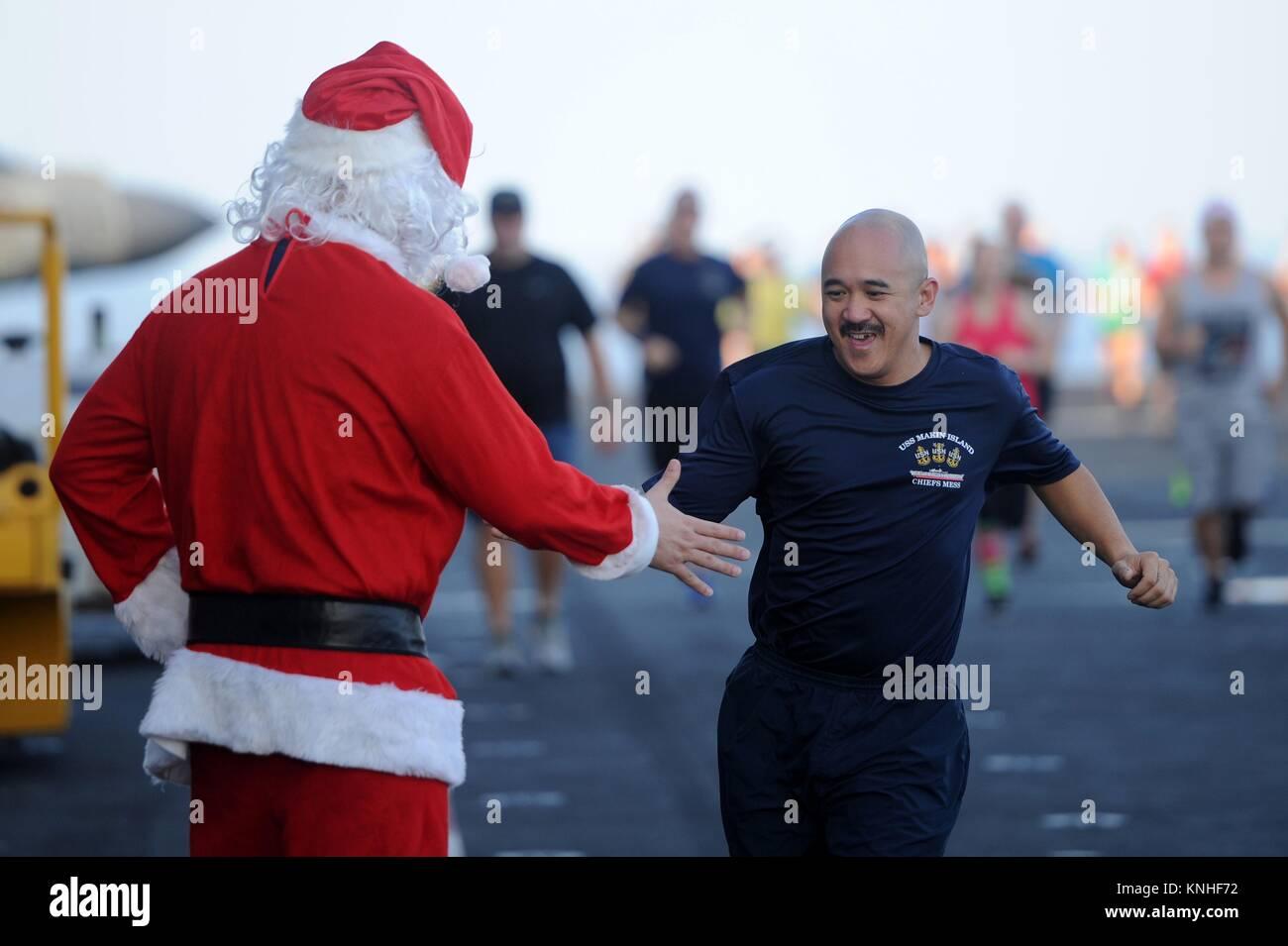 Ein Weihnachtsmann Imitator high-fives eine US-Sailor während der Weihnachten 5K laufen auf dem Flugdeck an Stockbild