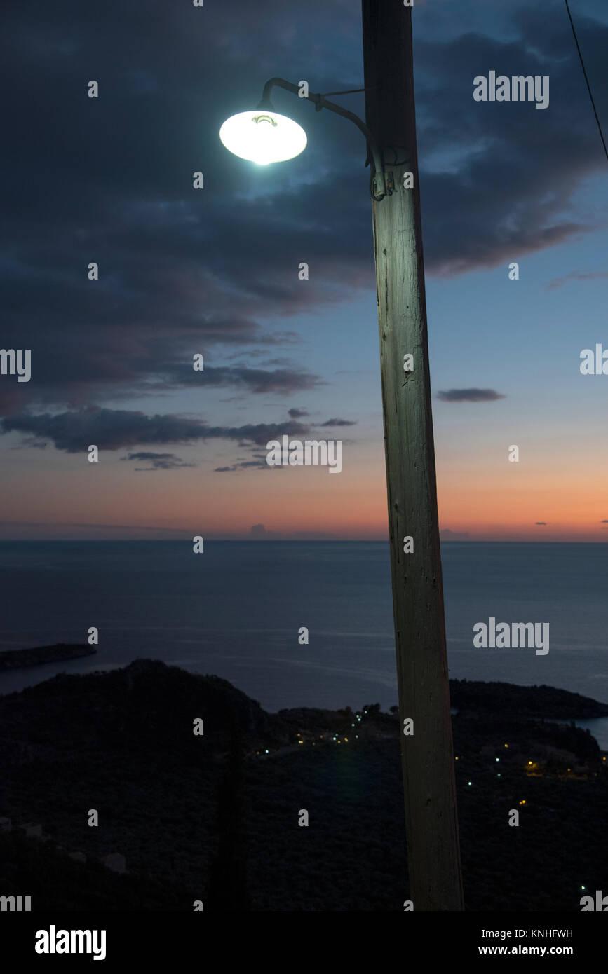 Straße Licht durch ein Fenster gegen einen stimmungsvollen Sonnenuntergang am Mittelmeer im Süden Griechenlands Stockbild