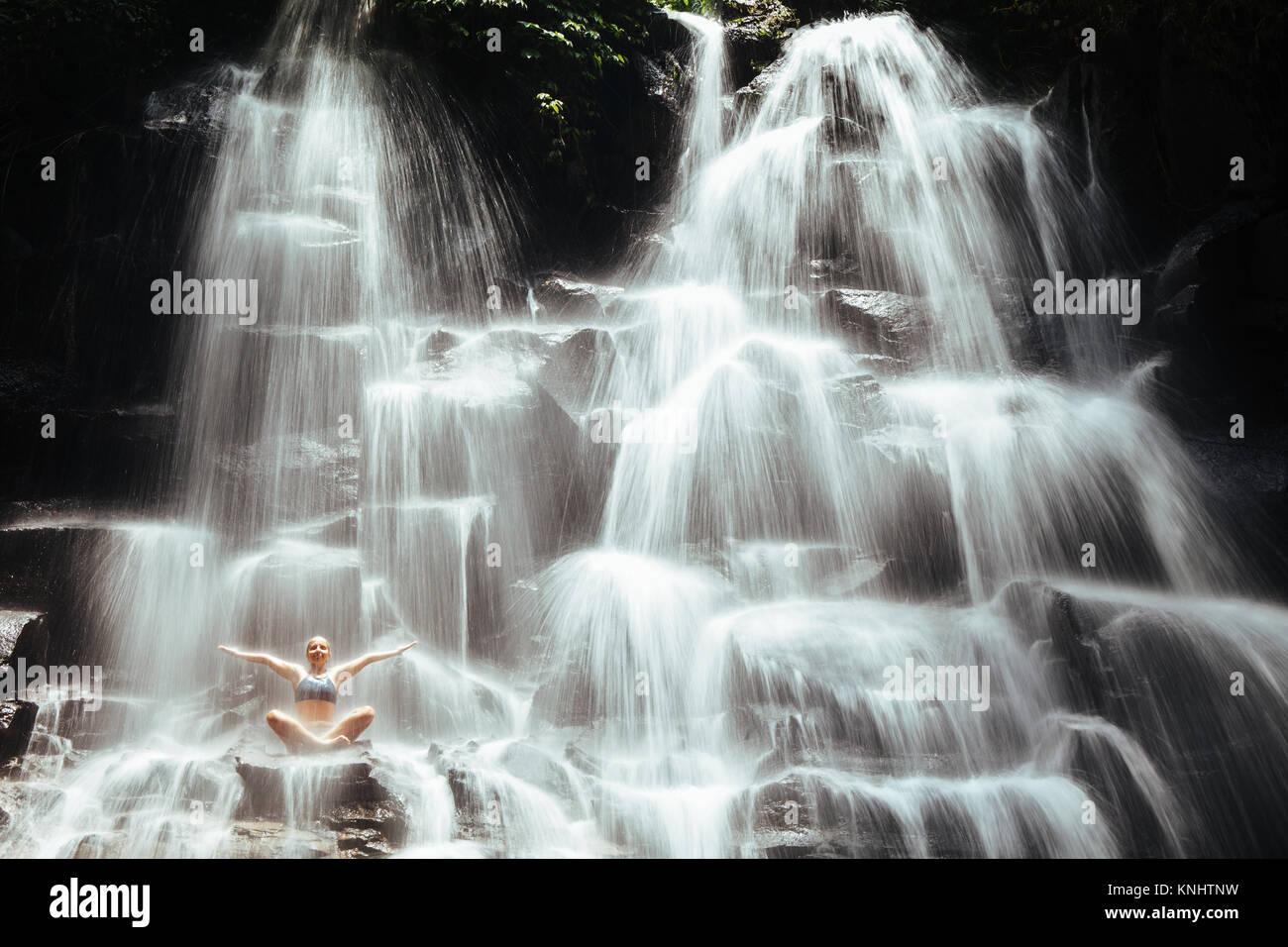 Reisen in Bali Dschungel. Schöne junge Frau in Yoga sitting Pose auf Fels unter der Feder Wasser, genießen Stockbild