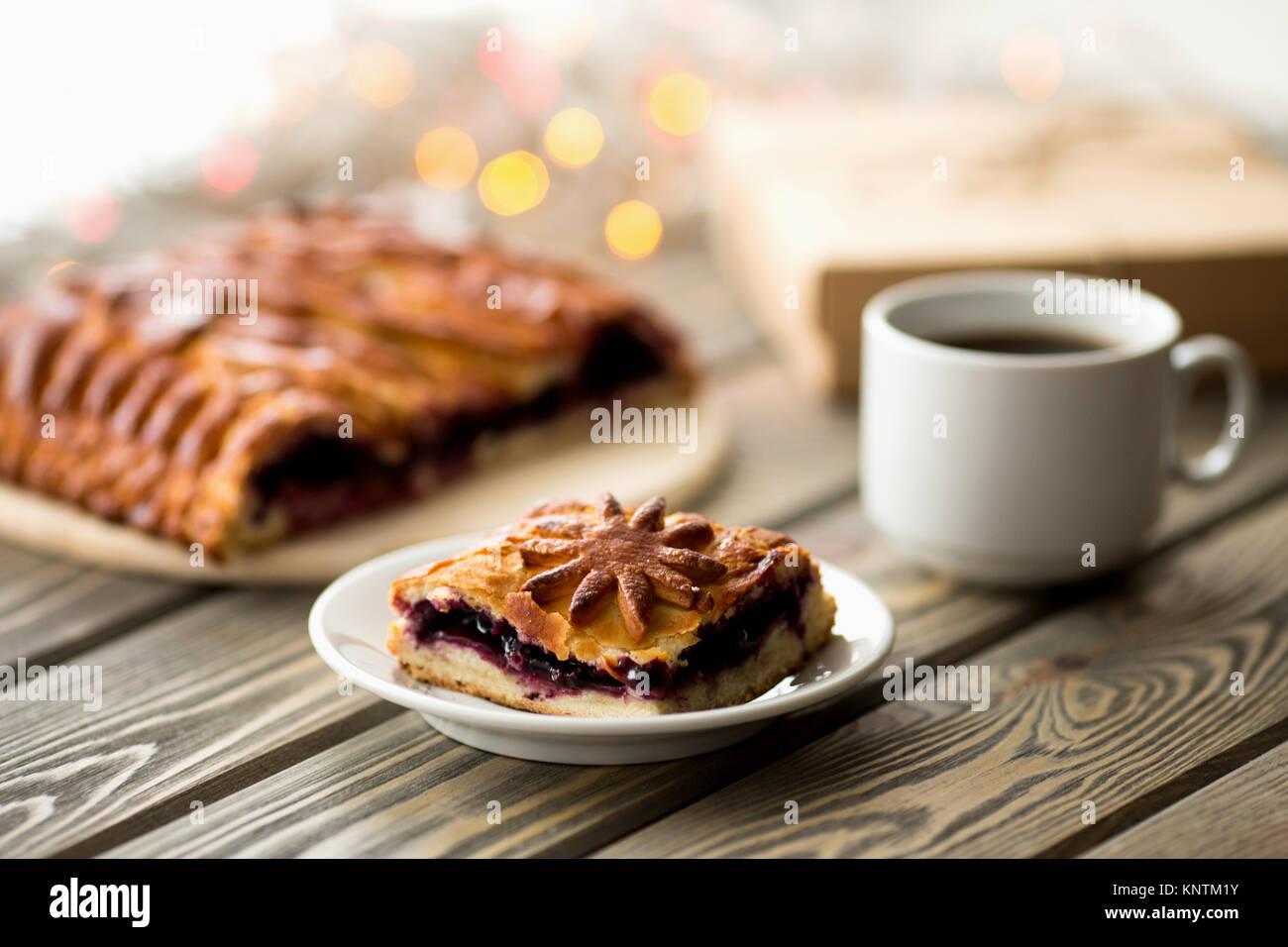 Stück Kuchen auf der Weihnachten Tabelle. Weihnachtsbeleuchtung und Dekoration. Süßigkeiten. Stockbild