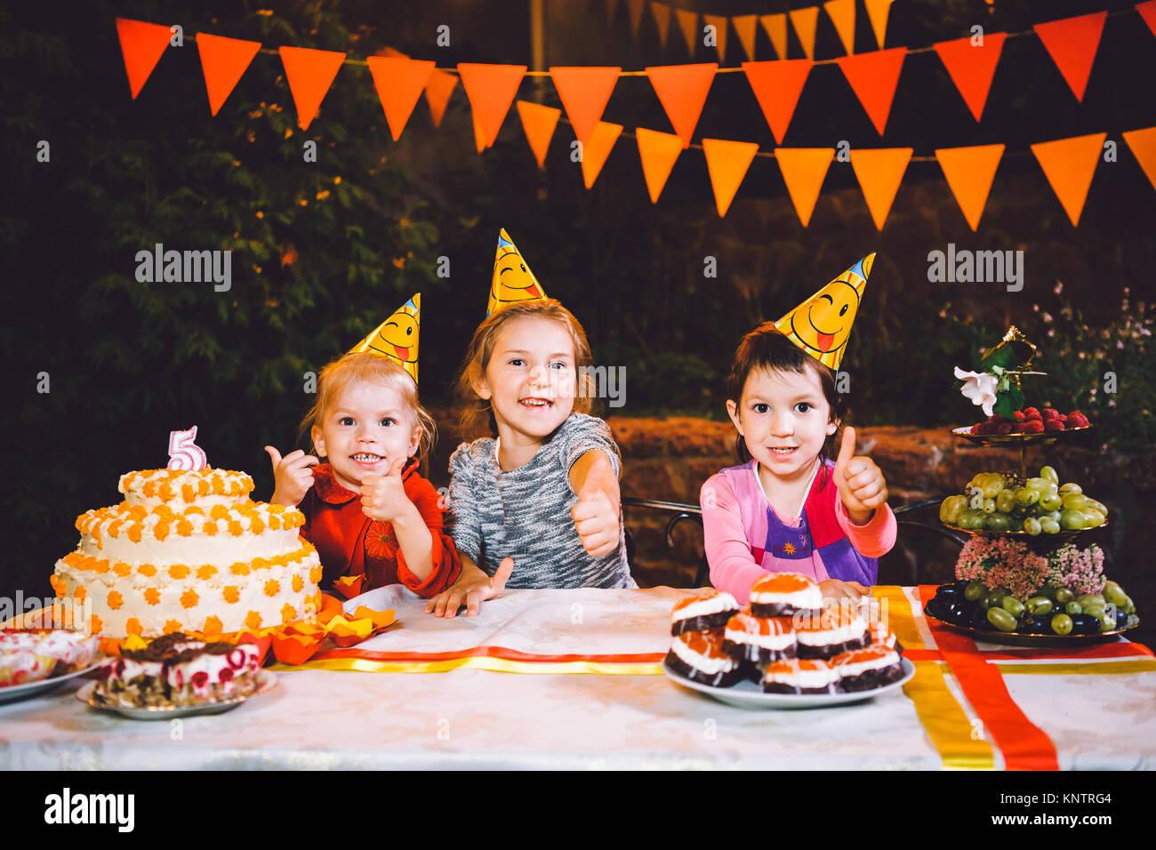 Kindergeburtstage. Drei fröhliche Kinder Mädchen Kuchen essen, mit ihren Händen und Verschmieren Stockbild