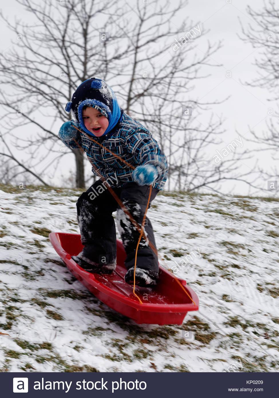 Ein kleiner Junge (5 Jahre alt) Snowboarden in seinem Schlitten stehen hinunter Hang. Stockbild