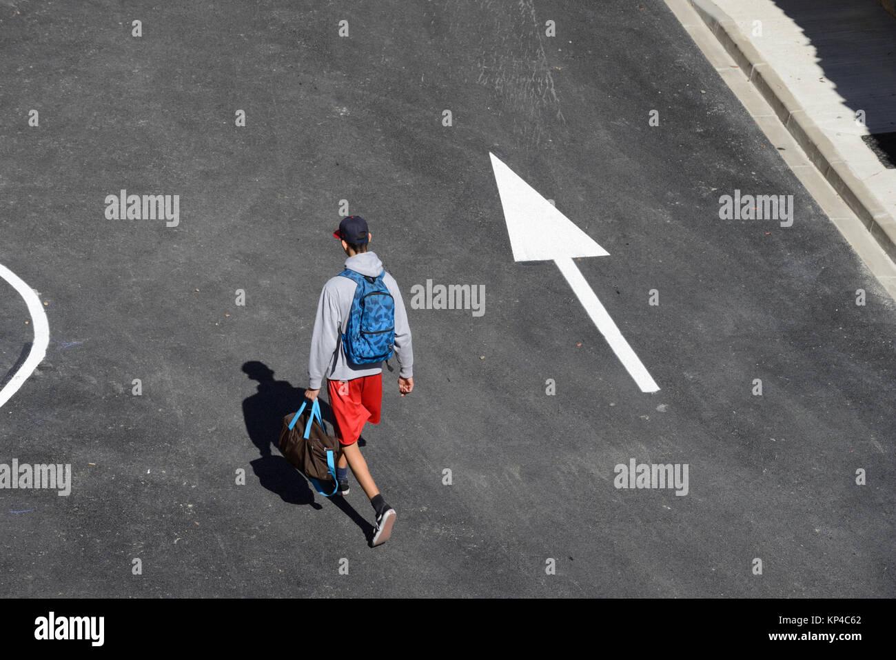 Mann zu Fuß die Straße runter nach Richtungspfeil Aigues-Mortes, Gard, Frankreich Stockbild
