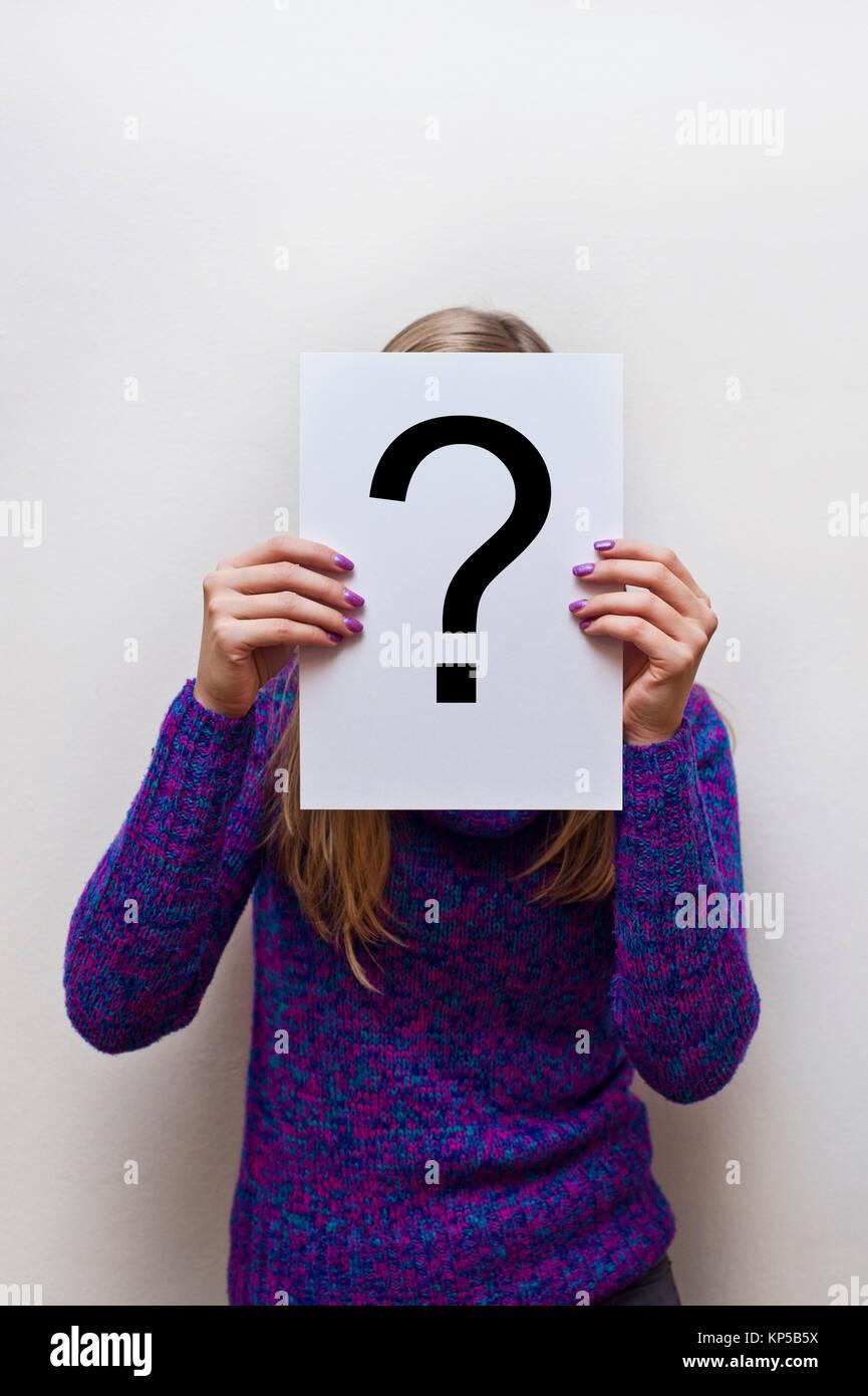 Frau in lila Pullover Holding ein Weißbuch mit einem Fragezeichen Stockbild