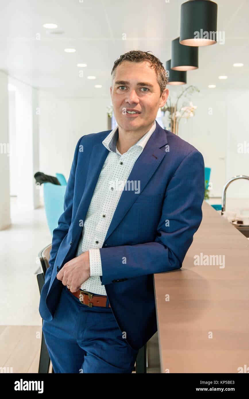 Geldrop, Niederlande. Editorial Porträt einer männlichen, kaukasische Banker an seine Bank - Office Rezeption. Stockbild