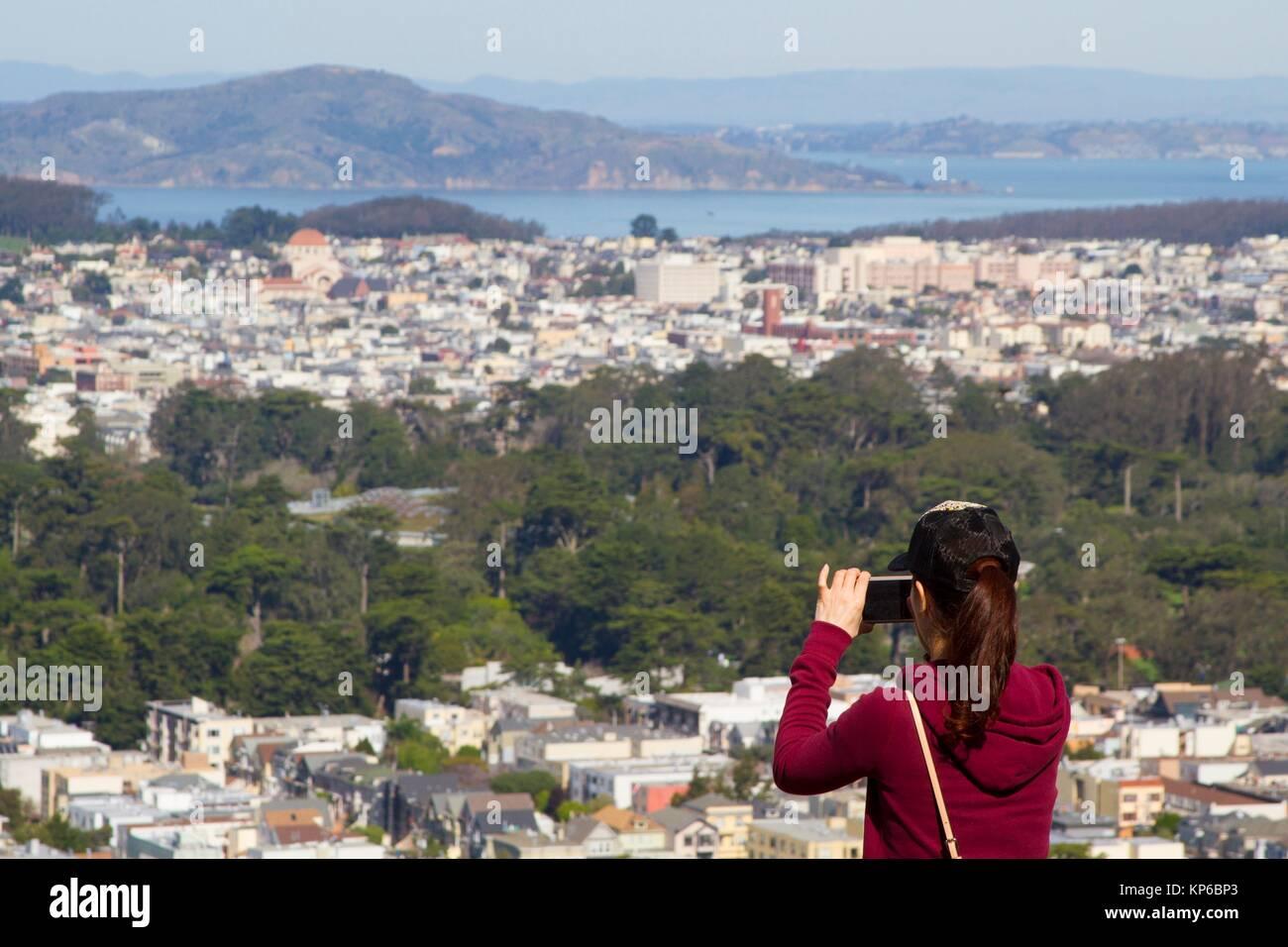 Kaukasische weibliche Touristen mit einer Baseball Cap und pferdeschwanz ein Foto mit Ihrem Handy auf die Skyline, Stockbild
