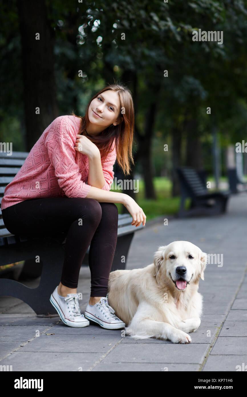 Foto von Frau sitzt auf der Bank am Spaziergang mit Hund Stockbild