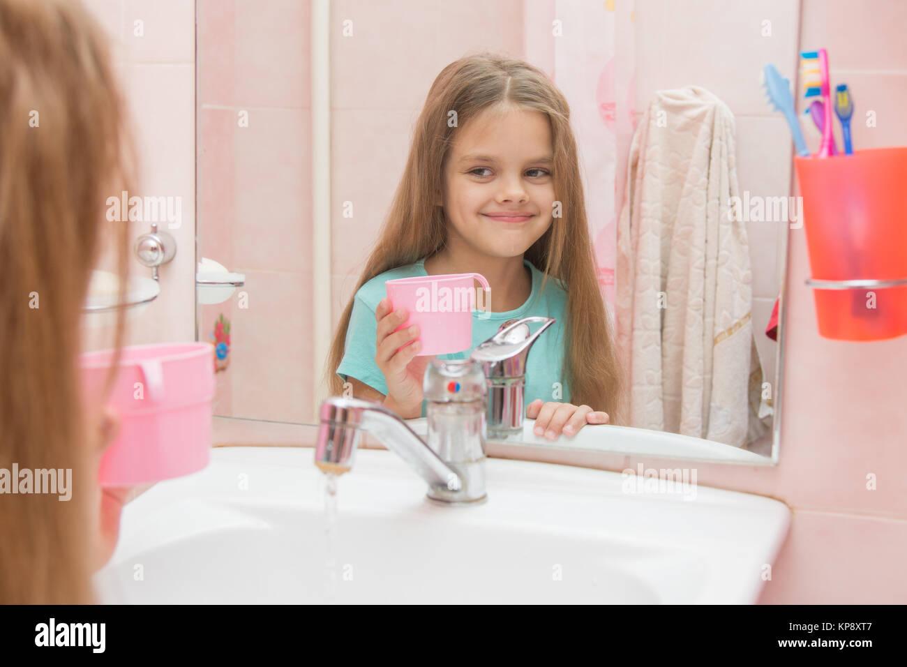 Glückliches Mädchen hält eine Tasse und schaut in den Spiegel im ...