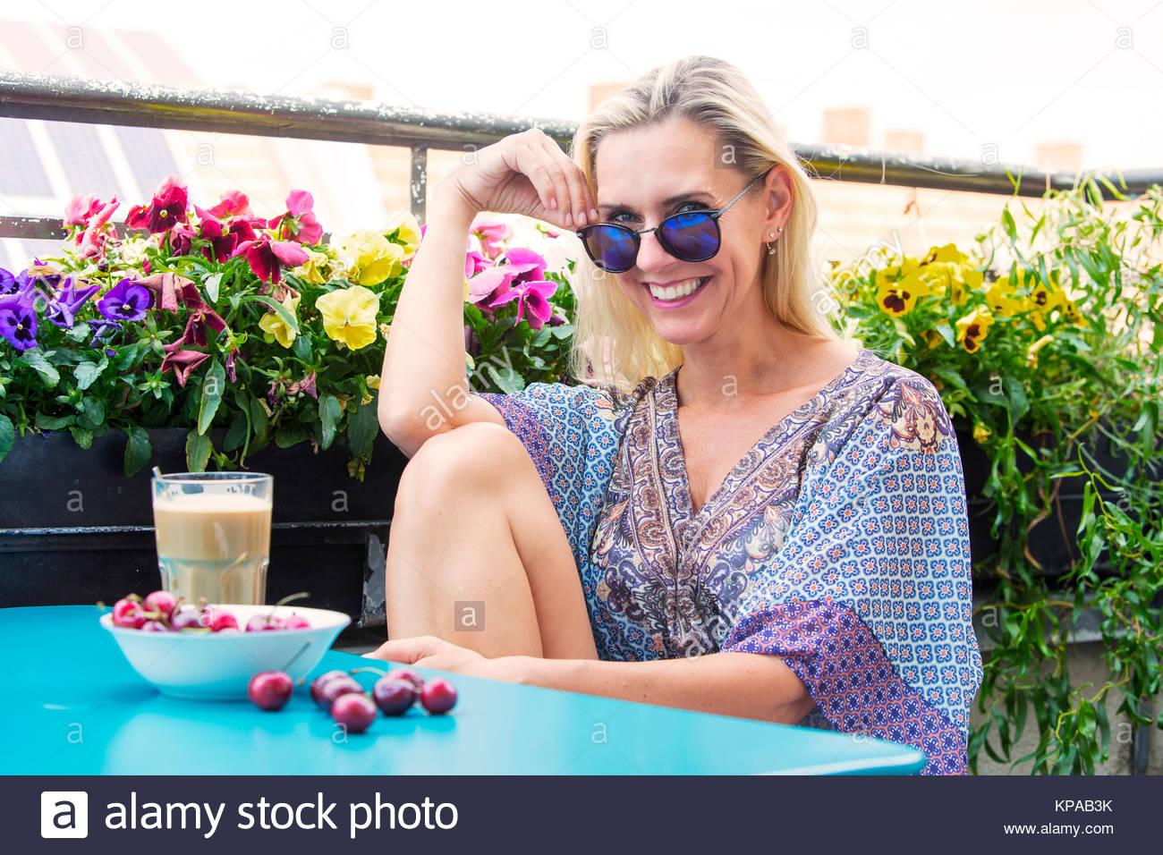 blonde frau sitzt auf dem balkon mit kaffee und kirschen stockfoto bild 168643991 alamy. Black Bedroom Furniture Sets. Home Design Ideas