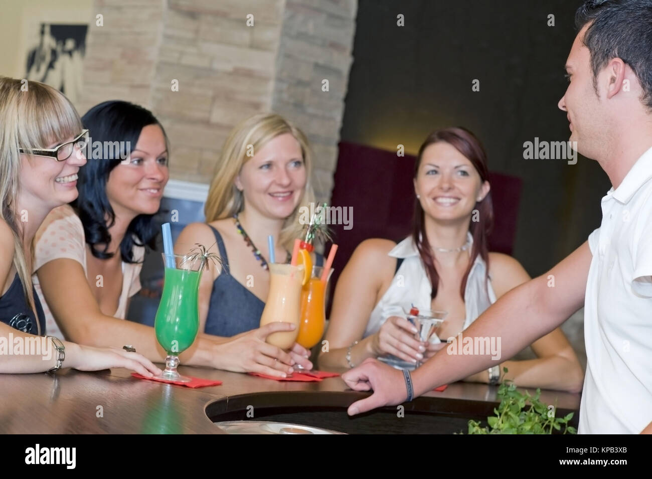 Model Release, Junger Kellner Flirtet Mit Vier Frauen eine der Bar - Barkeeper coquets mit vier Frauen an der bar Stockbild
