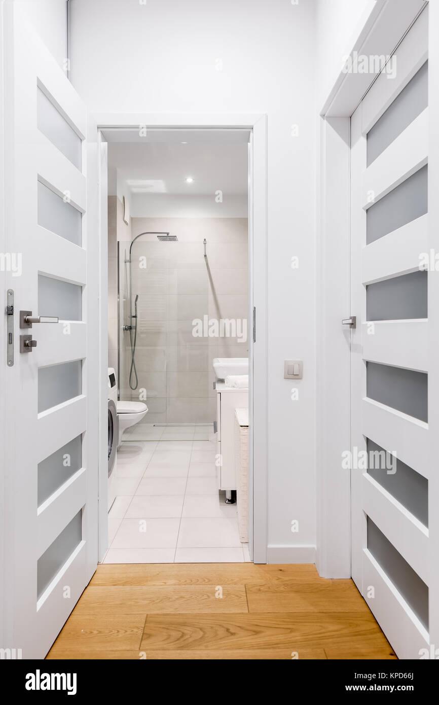 Langer Flur mit Parkettboden und offene Tür zum Badezimmer Stockfoto ...