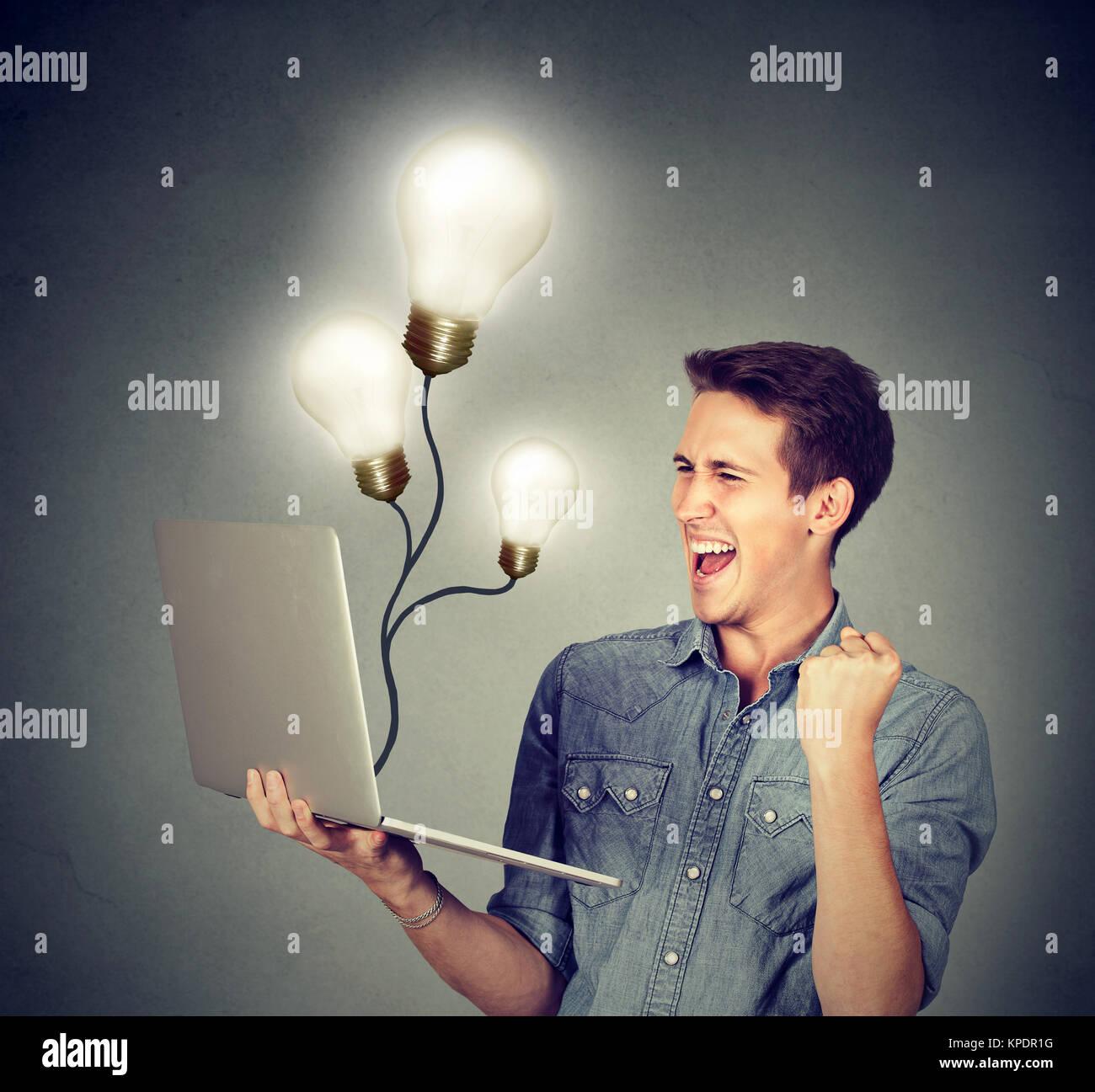 Junger Mann mit Laptop und Erfolge feiern tolle Ideen. Stockbild