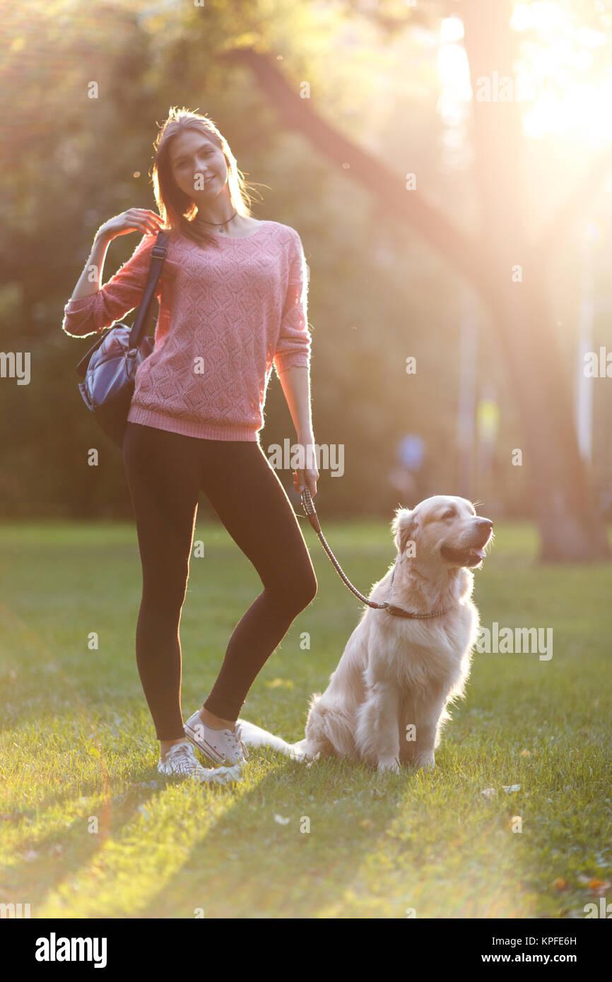 Foto der schönen Frau auf Spaziergang mit Hund im Sommer Park Stockbild
