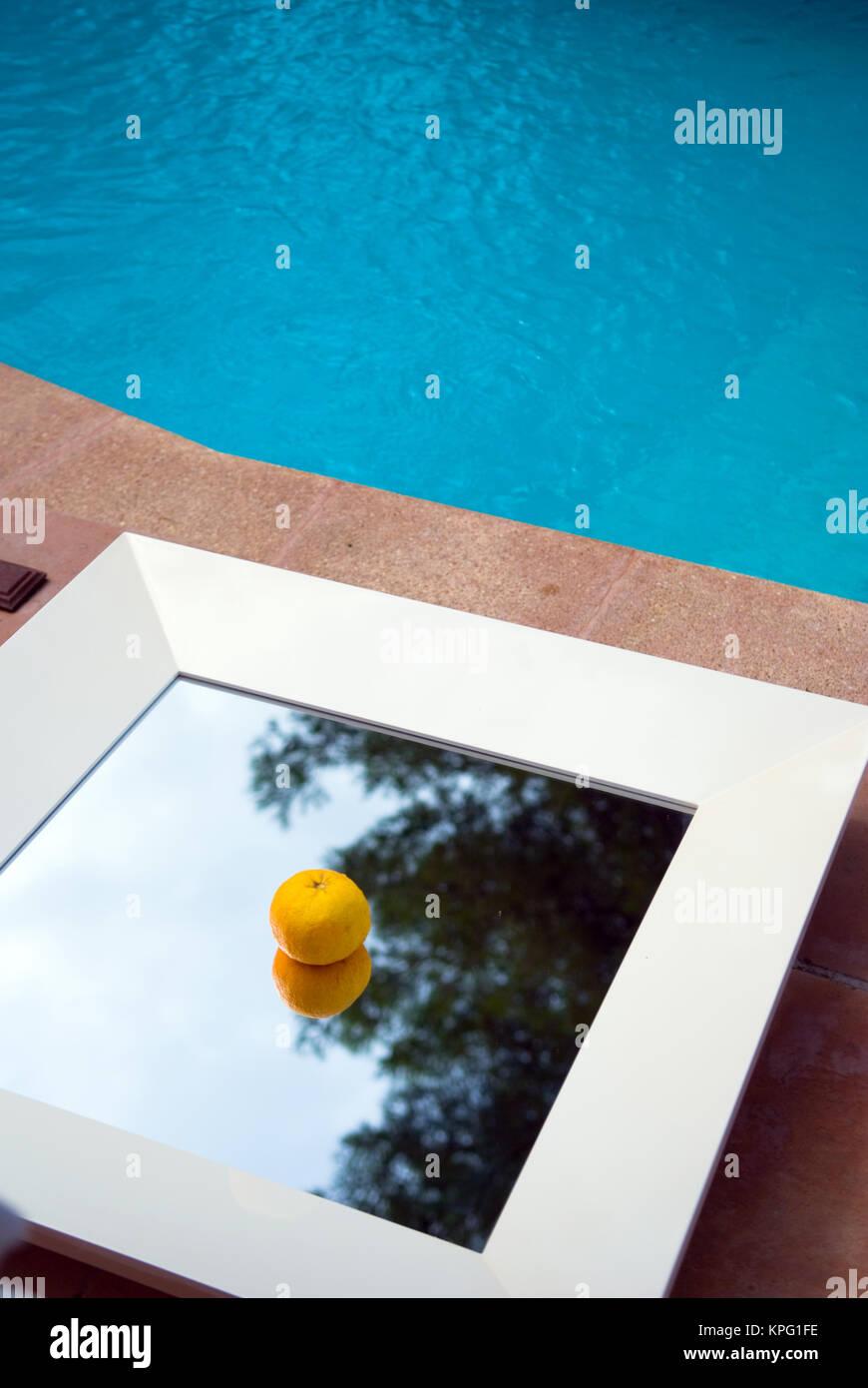 Eine einzelne orange sitzt auf einem Spiegel Tisch an der Seite von einem Pool Stockbild
