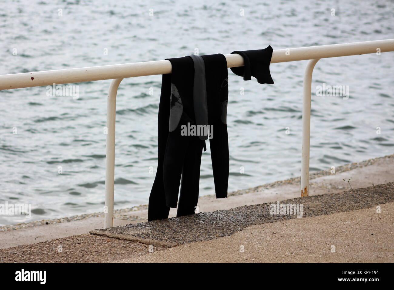 Nassen Schwarzen Und Grauen Anzug Links Auf Weissem Metall Zaun Neben