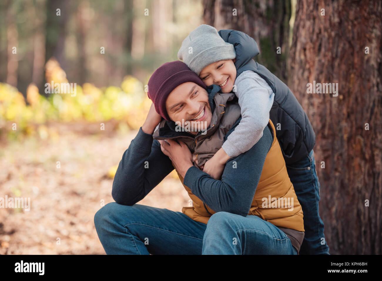 Vater und Sohn umarmen im Wald Stockbild