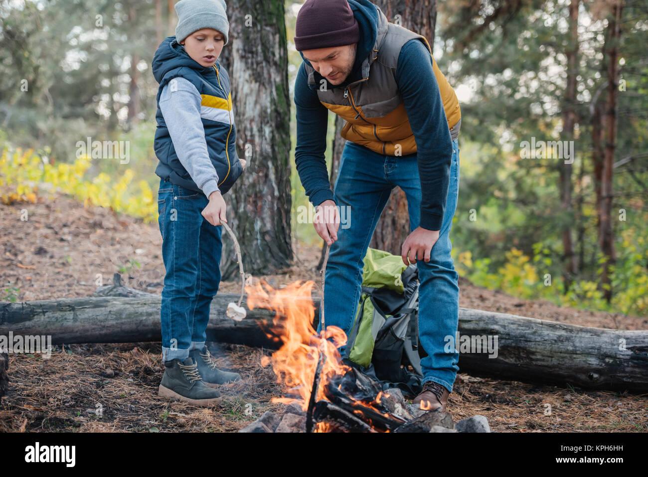 Vater und Sohn kochen Marshmallows in Wald Stockbild