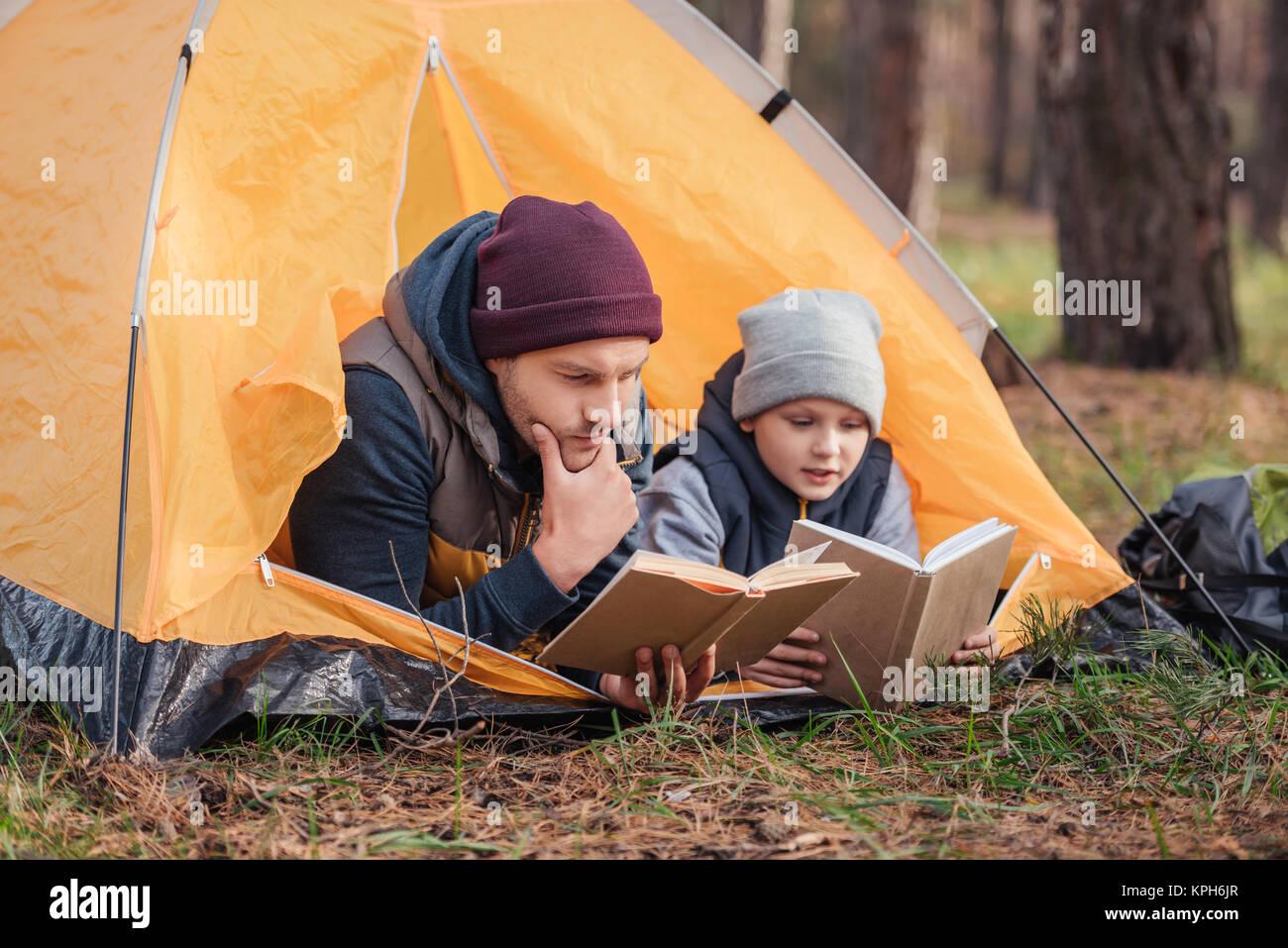 Vater und Sohn das Lesen von Büchern im Zelt Stockbild