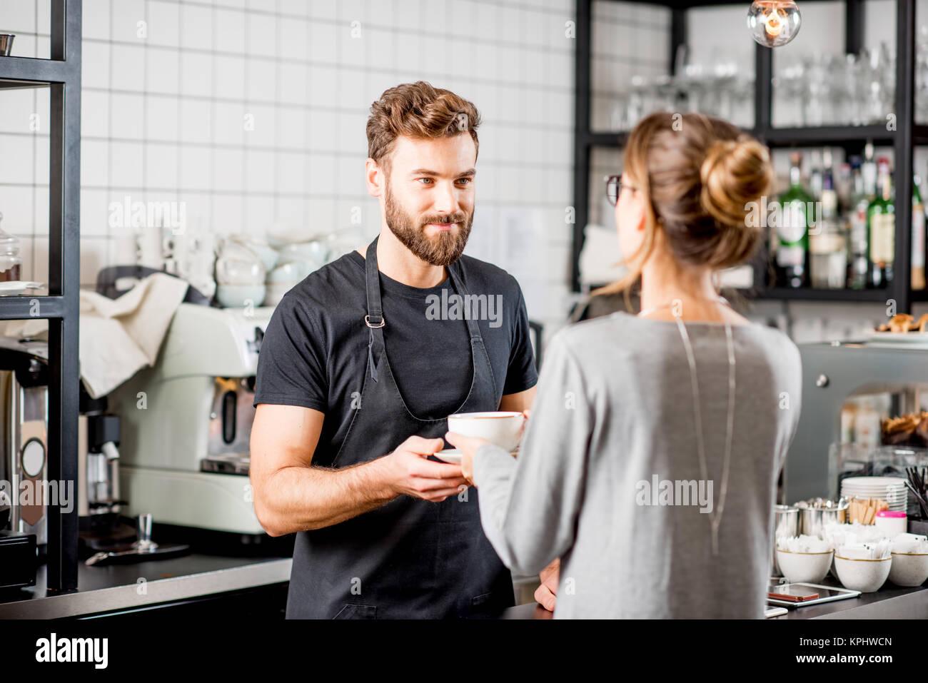 Barista mit Client im Cafe Stockfoto