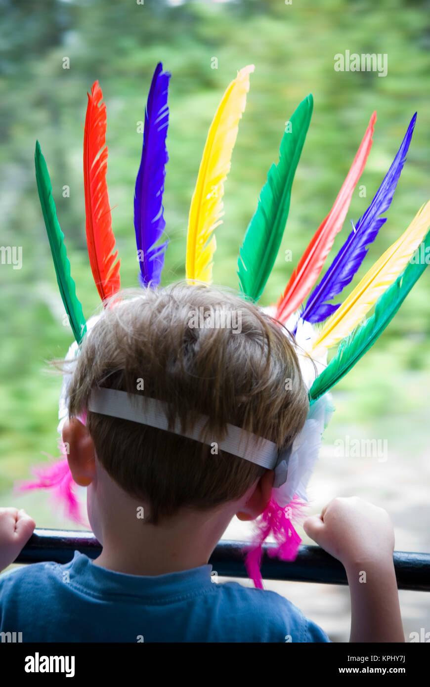 Hintere Aufnahme des Jungen aus der Zug Fenster mit seinem Kopf geschmückt mit bunten Federn headress Stockbild