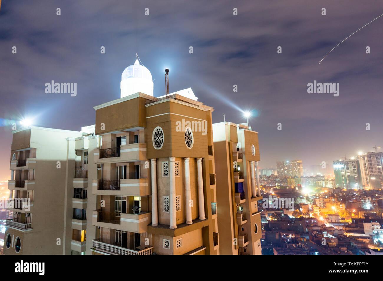 Skyscaper mit Wohnsitzen Schuß gegen die Noida Stadtbild an einem bewölkten Nacht. Diese Mehrstöckigen residence Stockfoto