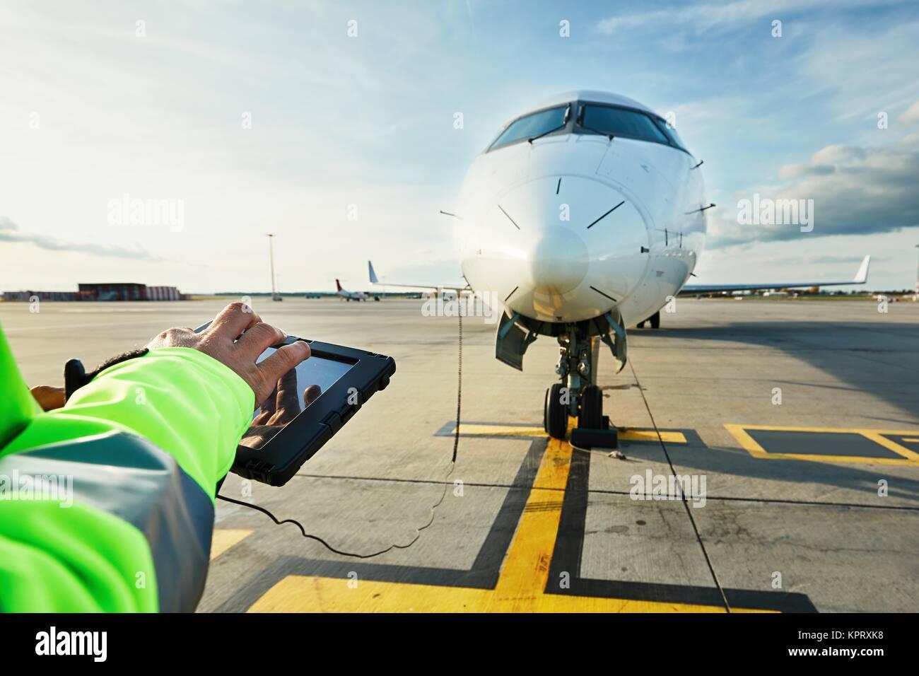 Moderne Technik am Flughafen. Mitglied des Bodenpersonals Vorbereitung der Passagier im Flugzeug vor dem Flug. Stockfoto