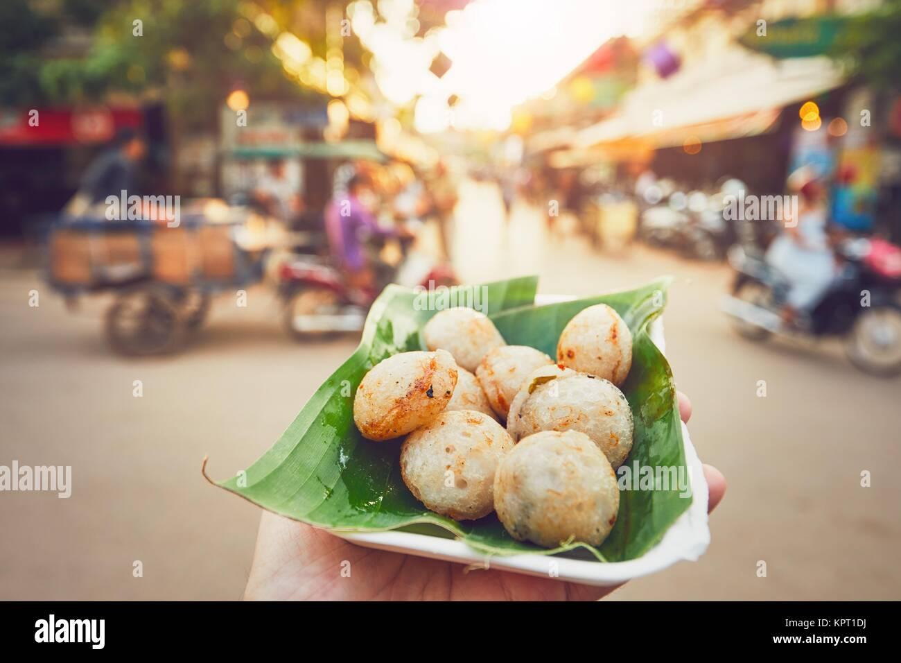 Hand der Mann hält Schüssel mit süßen Kokosnuss essen. Belebten Straße mit vielen Restaurants, Stockbild