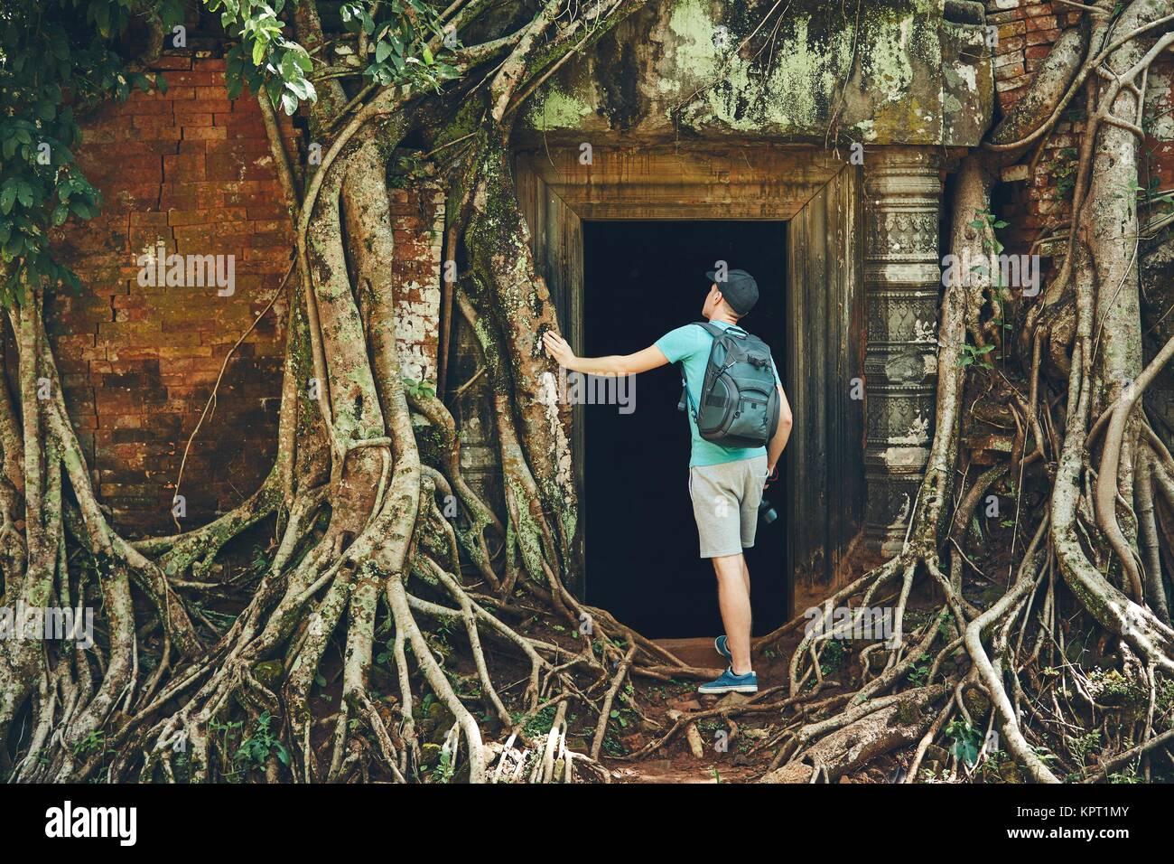 Junger Mann mit Rucksack zu antiken Monumente, die unter den riesigen Wurzeln des Baums in der Nähe von Siem Stockbild