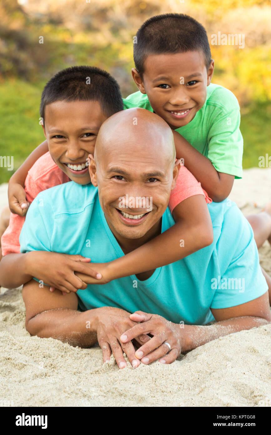 Vater mit seinen Kindern spielen am Strand. Stockfoto