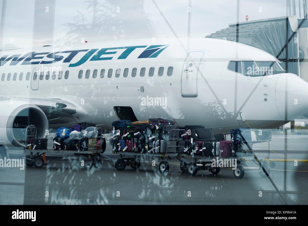 Künstlerische Foto von einem Gepäckträger Zug voller Gepäck über auf einem WestJet Flugzeug Stockbild