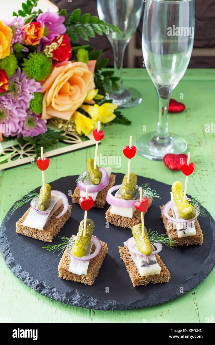 Kanapees mit Roggenbrot, Hering und Pickles auf einem festlich gedeckten Tisch. Valentinstag Konzept oder Hochzeit. Stockbild