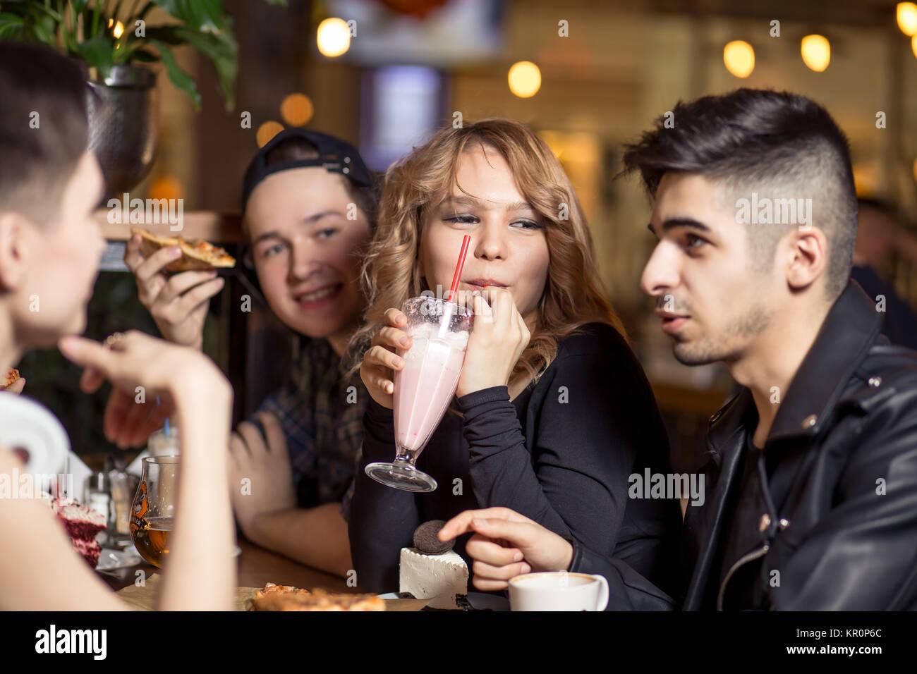 Junge Frau trinkt Milkshakes beim Sitzen mit Freunden im Cafe Stockbild