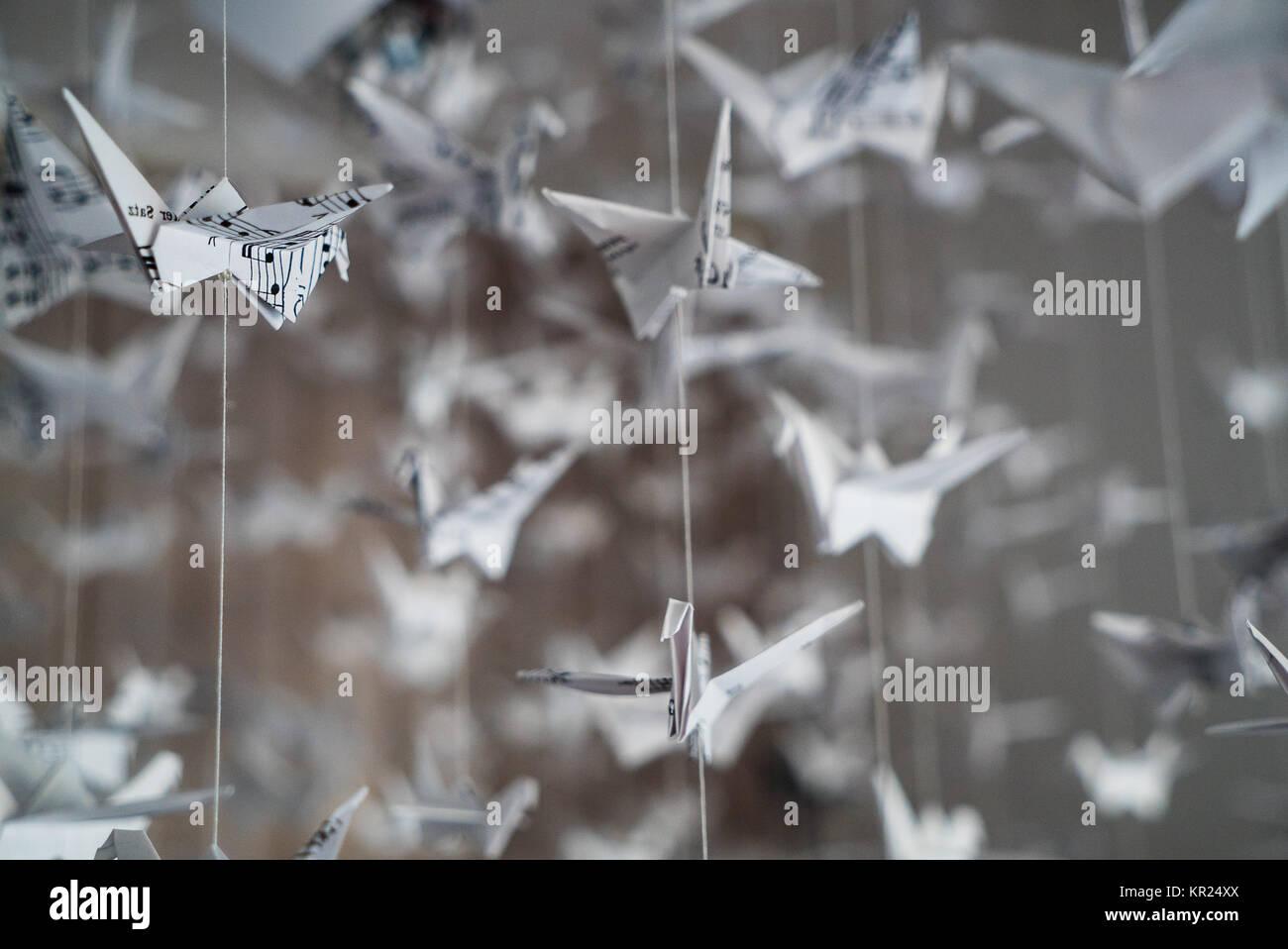 Schwarm von origami Kraniche aus Musik Manuskript Papier Stockfoto