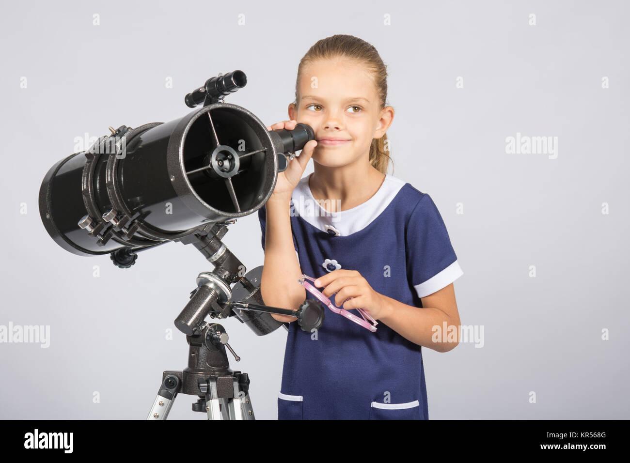 Siebenjährige Mädchen stehend nahe bei einem Spiegelteleskop und Blicke auf mysteriöse Weise in den Himmel Stockfoto