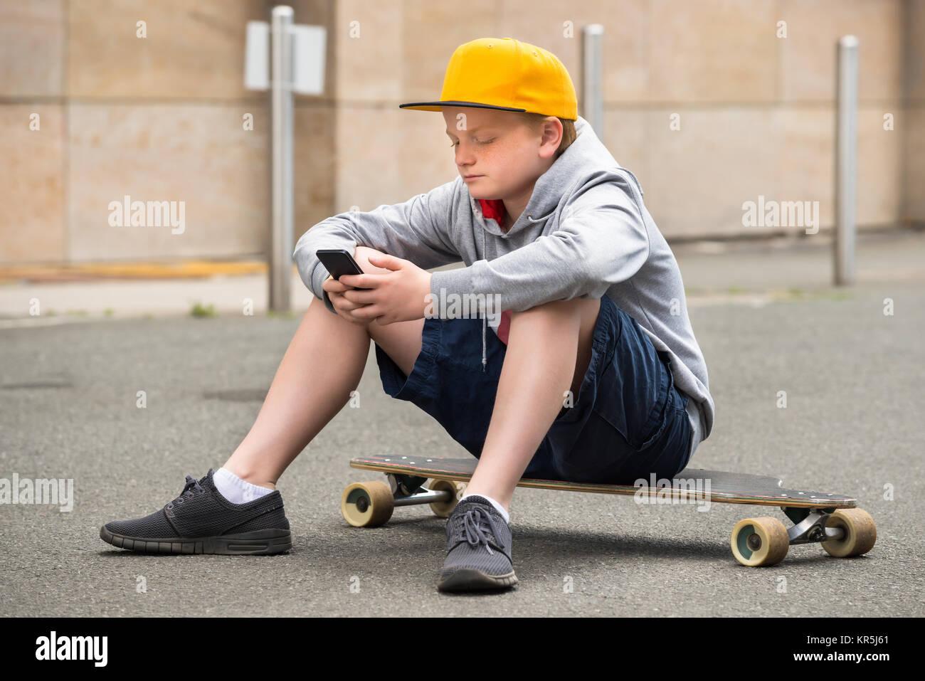 Junge tragen Sie die Kappe mit Smartphone Stockfoto