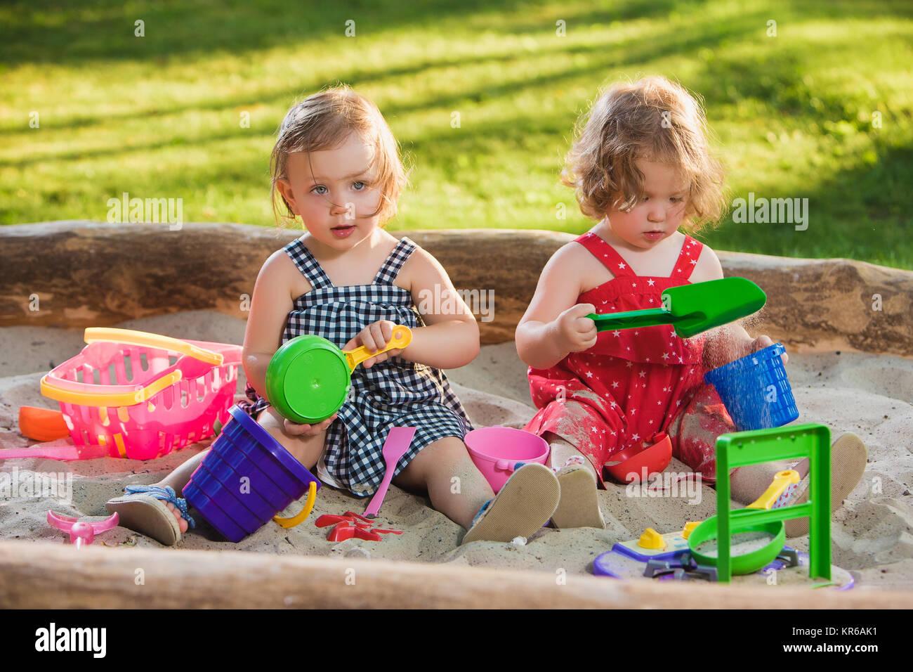 Die beiden baby wenig mädchen spielen spielzeug in sand