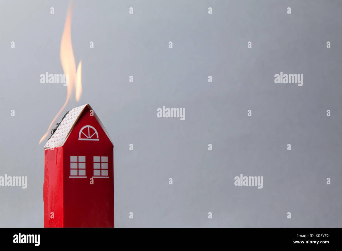 Haus Feuer Konzept. Spielzeug Haus mit Flammen Stockbild